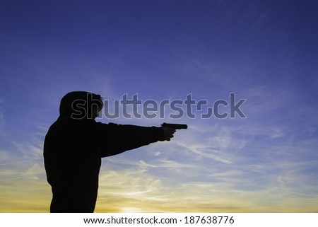 A young woman in a hoodie, holding a hand gun in a sunset. - stock photo