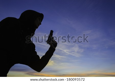 A young woman in a hoodie, holding a hand gun. / Woman holding gun - stock photo