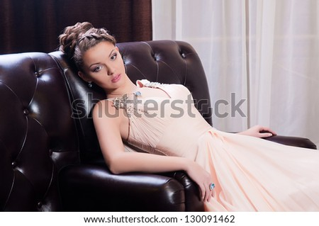 a young woman in a long sitting on the couch - stock photo