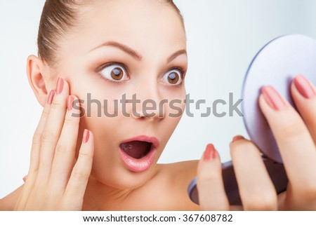 A young woman in a mirror treats acne on his face on a white background - stock photo