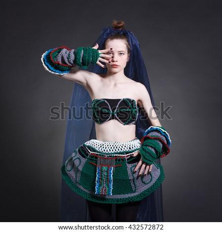 A young woman in a stylish and strange clothes. Fashionable photo.