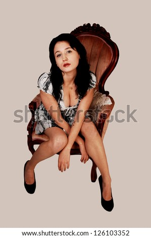 A young woman in an black and white dress and high heels sitting on an pink armchair, for white background. - stock photo