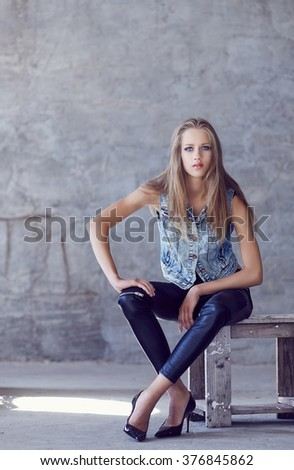 A young woman in denim jacket and black pants posing near concrete wall. - stock photo