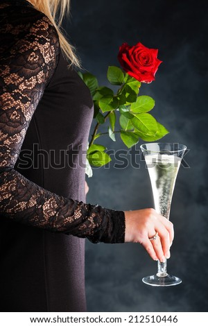 a young woman in evening dress with a red rose and a glass of sparkling wine or champagne. symbolic photo for valentine's day, romance and wedding day - stock photo