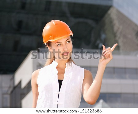 A young woman in hat, pointing up - stock photo