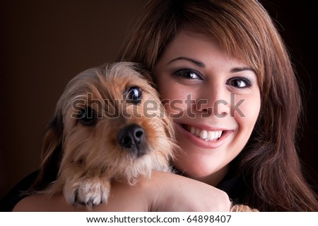 A young woman in her 20s holds a cute mixed breed beagle yorkshire terrier dog. - stock photo