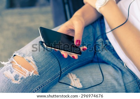 A young woman in jeans sitting on the bench and connect the headphones to her mobile phone. White smart phone is in female hands with a red manicure. Listening to music while walking. Retro colors. - stock photo