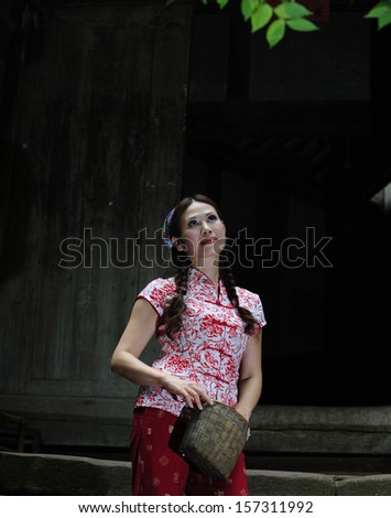a young woman in the courtyard of her home. - stock photo