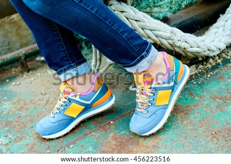 A young woman in white t-shirt and jeans, wearing fashion sports shoes, sitting on a rusty boat - stock photo