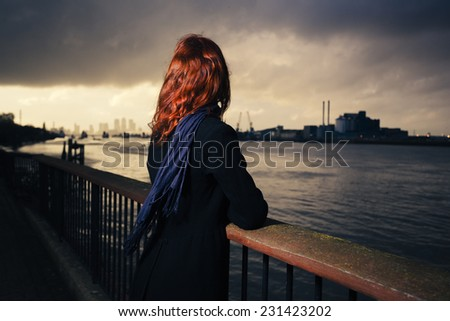 A young woman is admiring the sunset over a river in the city on a cold autumn day - stock photo