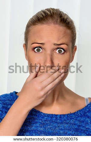 a young woman is afraid and looks scared - stock photo