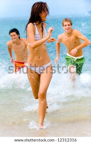 A young woman is being splashed at the beach by two male friends