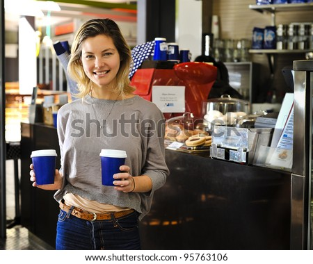 a young woman is buying takeaway coffees. - stock photo