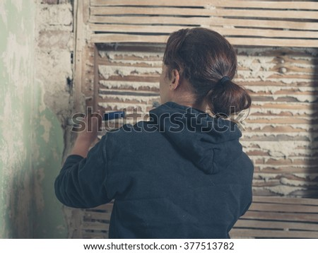 A young woman is chipping off the plaster on a wattle and daub wall with a hammer