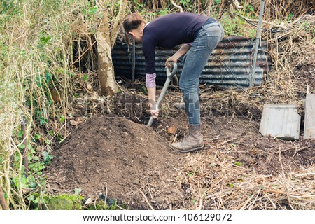 A young woman is digging a hole in a garden