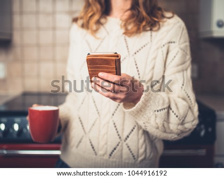 A young woman is drinking a cup of tea and using her smart phone in the kitchen