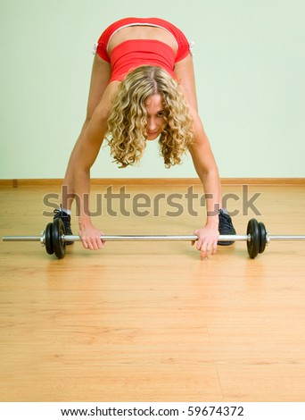 A young woman is engaged in weightlifting in the gym