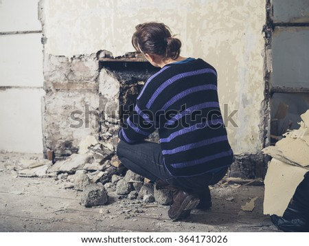 A young woman is examing a fireplace that has just been opened up