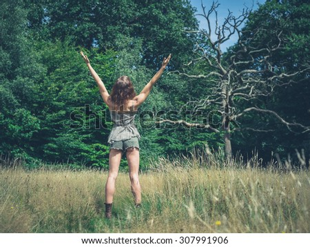 A young woman is expressing freedom by raising her arms in a meadow in the forest - stock photo