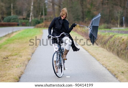 A young woman is fighting against the storm on her bicycle