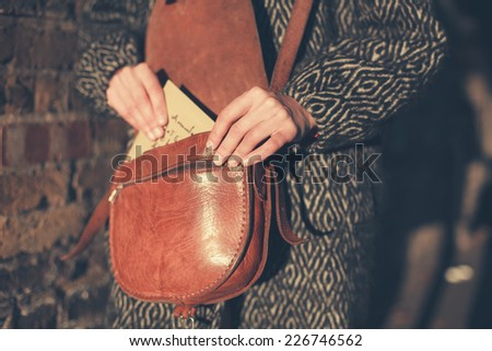 A young woman is getting a letter out of her bag at sunset as she is walking in the street - stock photo