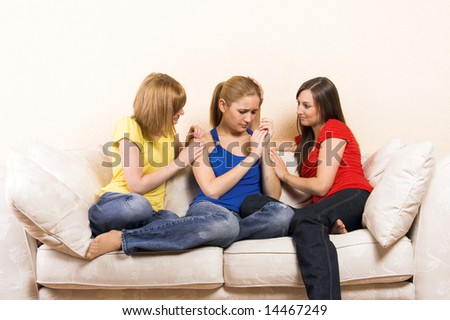 a young woman is having problems and is comfort by her girlfriends - stock photo