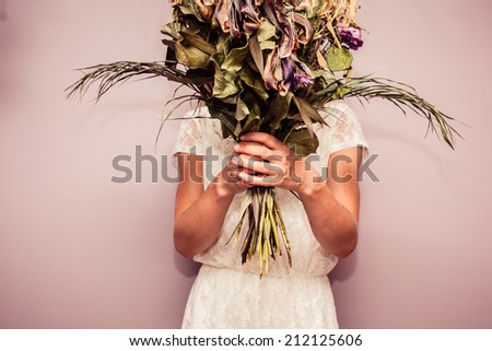 A young woman is holding a bouquet of dead flowers - stock photo