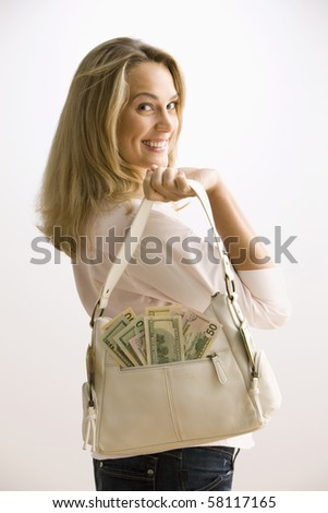 A young woman is holding a cash filled purse with large smile on her face.  Vertical shot. - stock photo