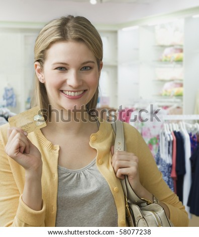 A young woman is holding a credit card up and smiles at the camera.  She is standing in a clothing store.  Vertical shot. - stock photo