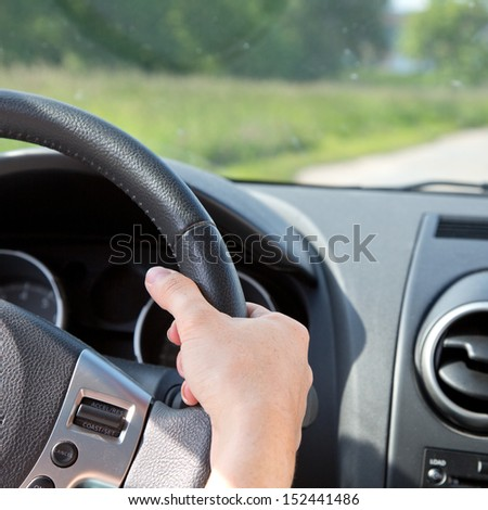 A young woman is holding the steering wheel of a car while driving - stock photo