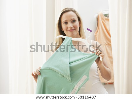 A young woman is holding up a dress to her body while shopping for clothes.  Horizontal shot. - stock photo