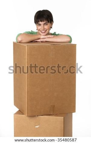 A young woman is leaning on some moving boxes and smiling at the camera.  Vertically framed shot.