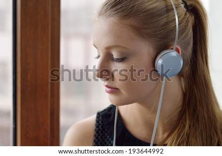 A young woman is listening to the music in the headphones indoors.