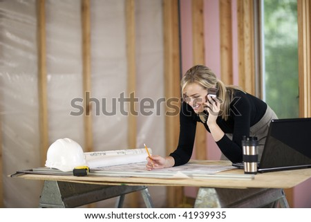 A young woman is looking at blueprints and talking on the phone.  She is working at a construction site.  Horizontally framed shot. - stock photo
