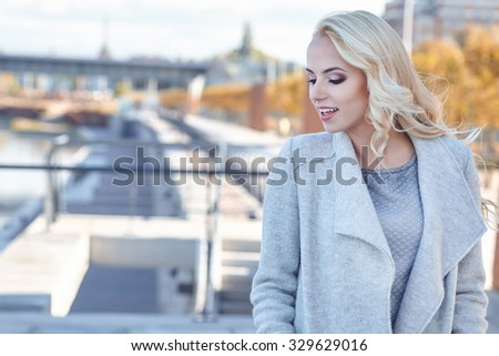A young woman is looking at the sunset over a river in the city  - stock photo