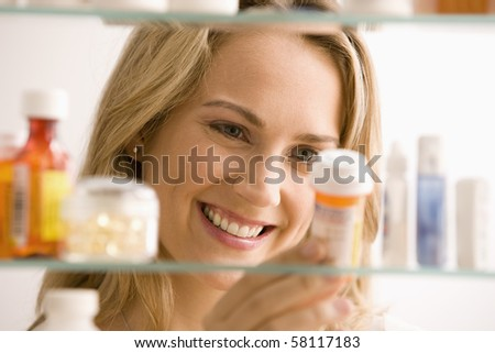 A young woman is looking through her medicine cabinet and smiling.  Horizontal shot.