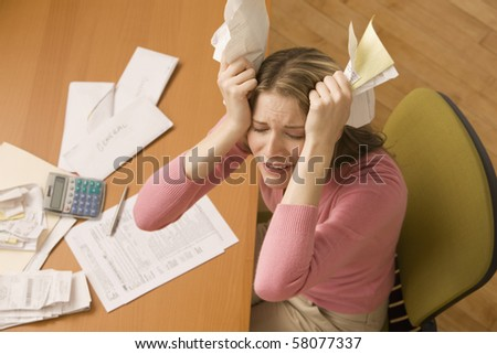 A young woman is paying bills at her desk and has her eyes closed from stress.  Horizontal shot. - stock photo