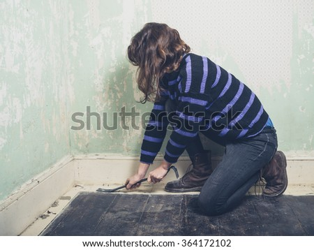 A young woman is prying the nails in her floorboards with a crowbar - stock photo
