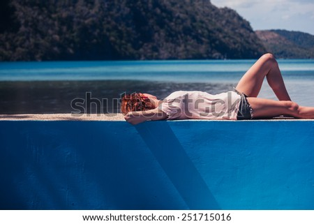 A young woman is relaxing by an empty  swimming pool and the  beach - stock photo