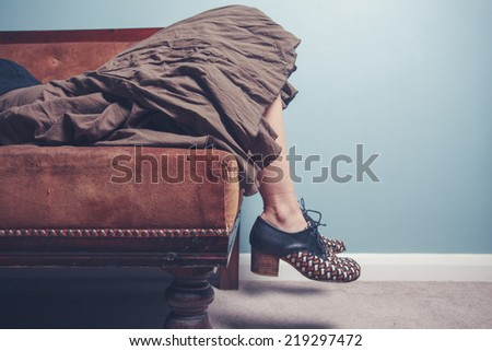 A young woman is relaxing on a sofa - stock photo