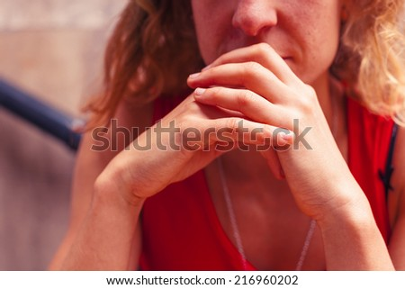 A young woman is resting her head on her hands in thought and contemplation - stock photo