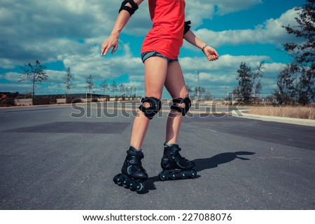 A young woman is rollerblading on a sunny day - stock photo