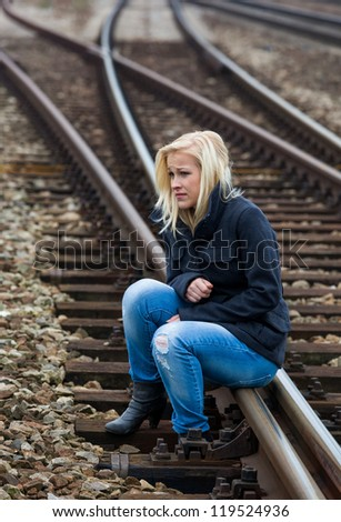 a young woman is sad, anxious and depressed. sitting on a track and is lonely - stock photo