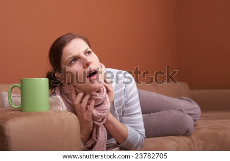 A young woman is sick. She is lying on the couch and is sneezing. She has a tea. A lot of copyspace.