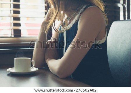 A young woman is sitting by the window in a diner and is having a cup of coffee - stock photo