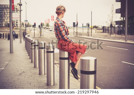 A young woman is sitting on a bollard by the roadside in the city - stock photo