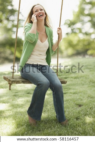 A young woman is sitting on a swing as she talks on her cellphone.  Vertical shot. - stock photo