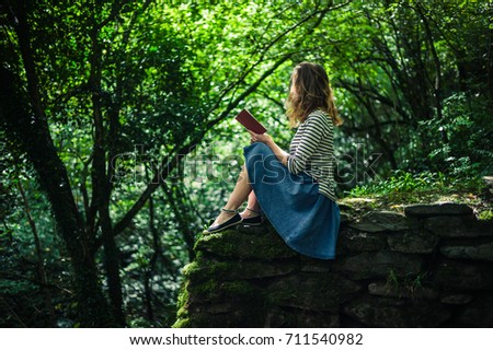 A young woman is sitting on a wall in the forest and is reading a book