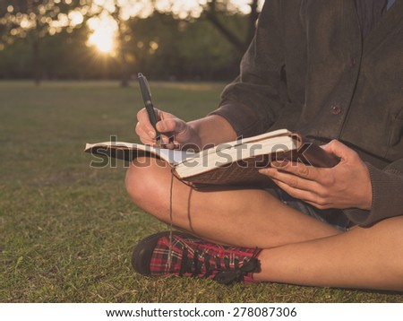 A young woman is sitting on the grass in a park at sunset and is writing in a notebook - stock photo