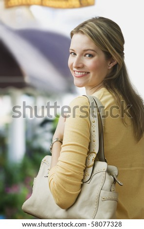 A young woman is smiling over her shoulder at the camera and is carrying a purse.  Vertical shot. - stock photo